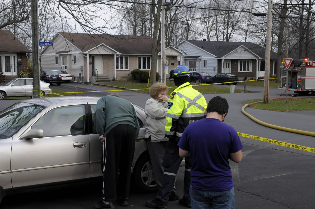Margaret Booth wipes her eyes as she talks to a paramedic at the scene of a semi-detachment home fire on Oran Ave. Her husband, Jerry, (left) checks on their dog in a car. (Cornwall Newswatch)