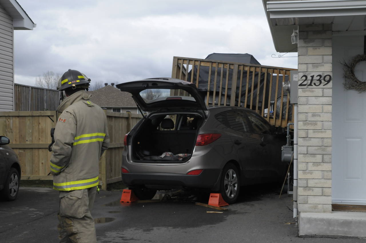 A Cornwall firefighter surveys the damage to a raised deck after an SUV plowed into it on Nov. 7. The woman driving escaped injury. (Cornwall Newswatch)