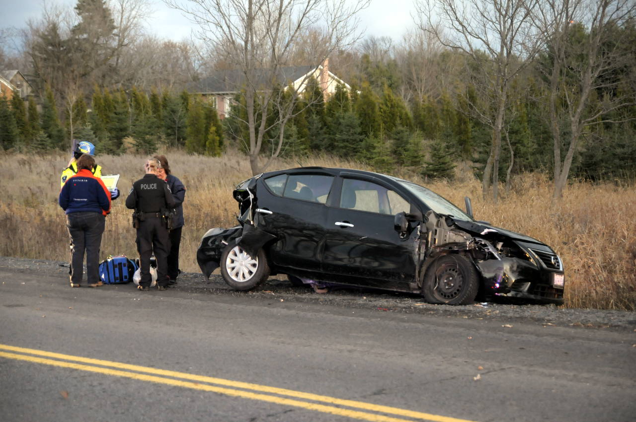 Police and a paramedic talk with two women in a Nissan Sentra involved in a three-vehicle collision on Cornwall Centre Rd. on Nov. 24, 2014. (Bill Kingston/Cornwall Newswatch)