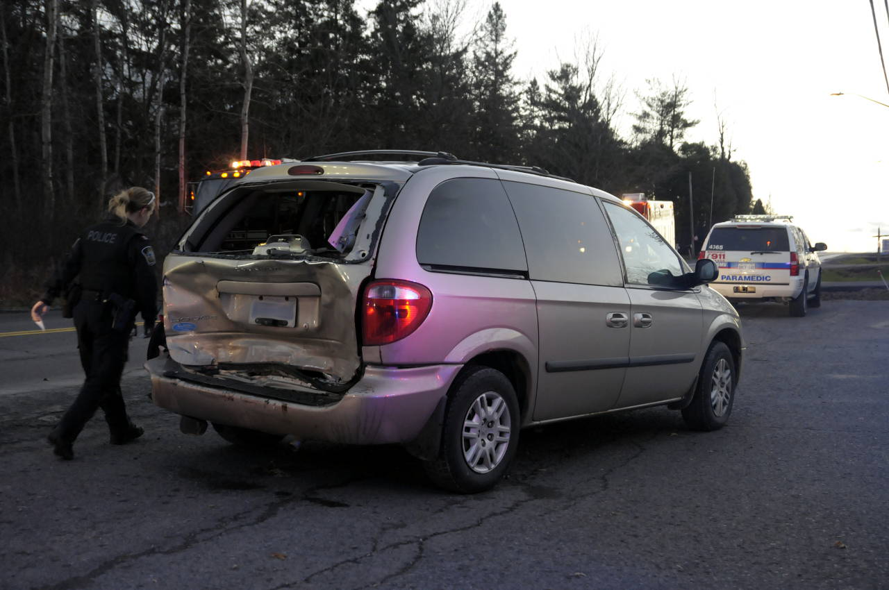 A police officer walks back to her cruiser after surveying the damage on this Dodge Caravan. (Bill Kingston/Cornwall Newswatch)