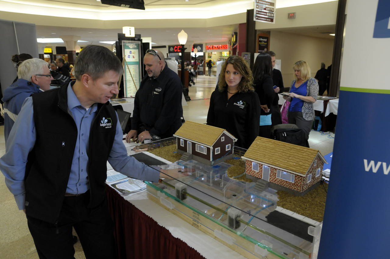 City of Cornwall Infrastructure GM John St. Marseille shows off a model illustrating how changes under the flood rebate program will improve water flow for the city and the homeowner. Flood rebate coordinator Tracy Gordon (right) watches the presentation. (Cornwall Newswatch)