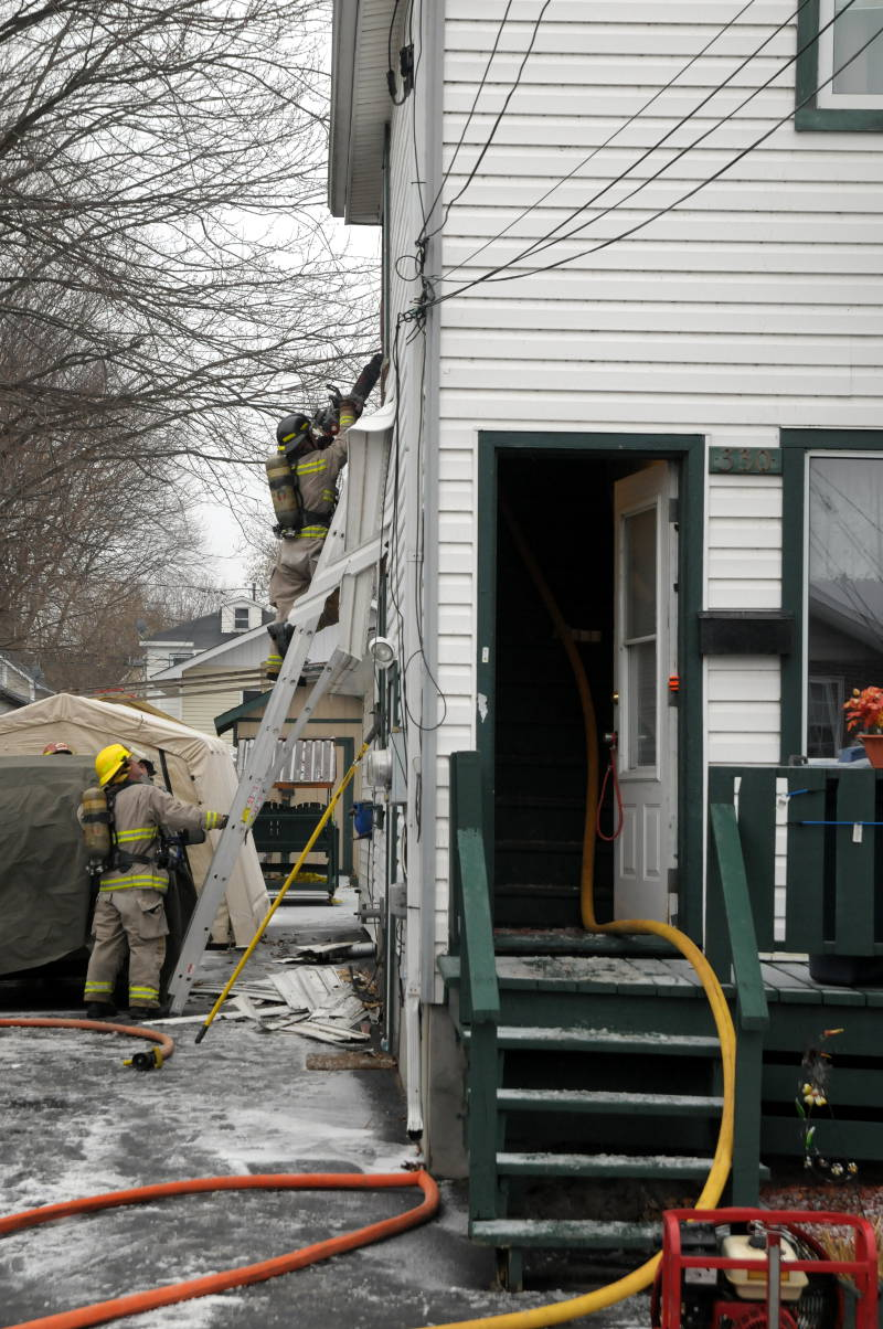 A Cornwall firefighter readies his chainsaw while another holds the ladder. The fire department was trying to put out a fire in a wall of this home on Eighth St. W on Dec. 6, 2014. (Cornwall Newswatch/Bill Kingston)