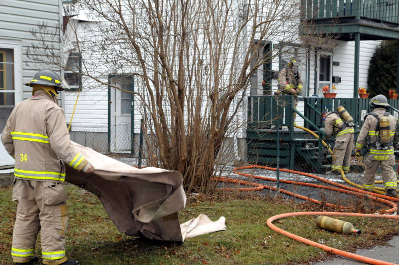 One firefighter, left, gets a blanket ready to lay down their equipment while three others, right, get their breathing gear ready to enter the home. The duplex on Eighth St. West had a fire in a wall on Dec. 6, 2014. (Cornwall Newswatch/Bill Kingston)