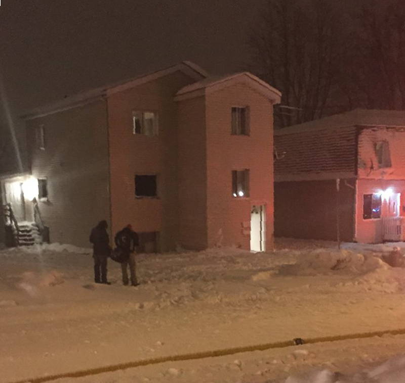 Two people, unidentified, stand outside this multi-residental building. There was a fire at this home at 109 Lefebvre Ave. around 7 p.m. on Dec. 11, 2014 which sent two people to hospital. (Photo/Jacob Dubois)