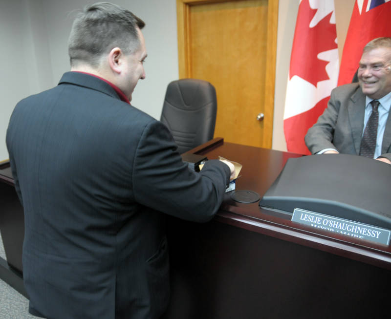 Coun. David Murphy, left, picks up his mail room key while talking to Mayor Leslie O'Shaughnessy, right, during a Dec. 16, 2014 meeting. Murphy is concerned the new security will make people reluctant to write to city hall. (Cornwall Newswatch/Bill Kingston)