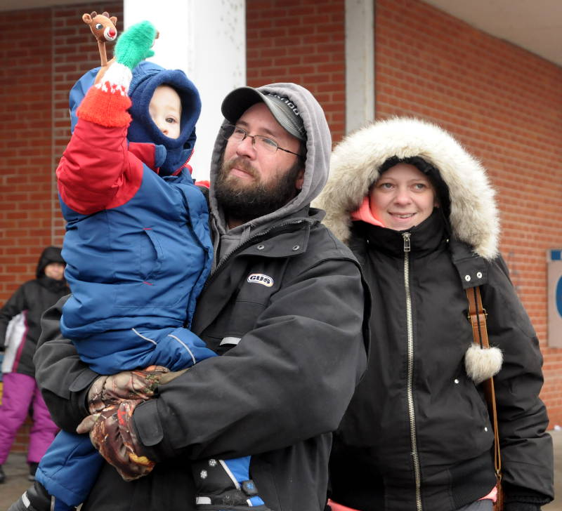 Kadan Summers, 22 months, of Iroquois waves to Santa Claus while his parents, Andrew and Amanda, watch the 21st annual Morrisburg Santa Claus Parade on Dec. 6, 2014. (Cornwall Newswatch/Bill Kingston)