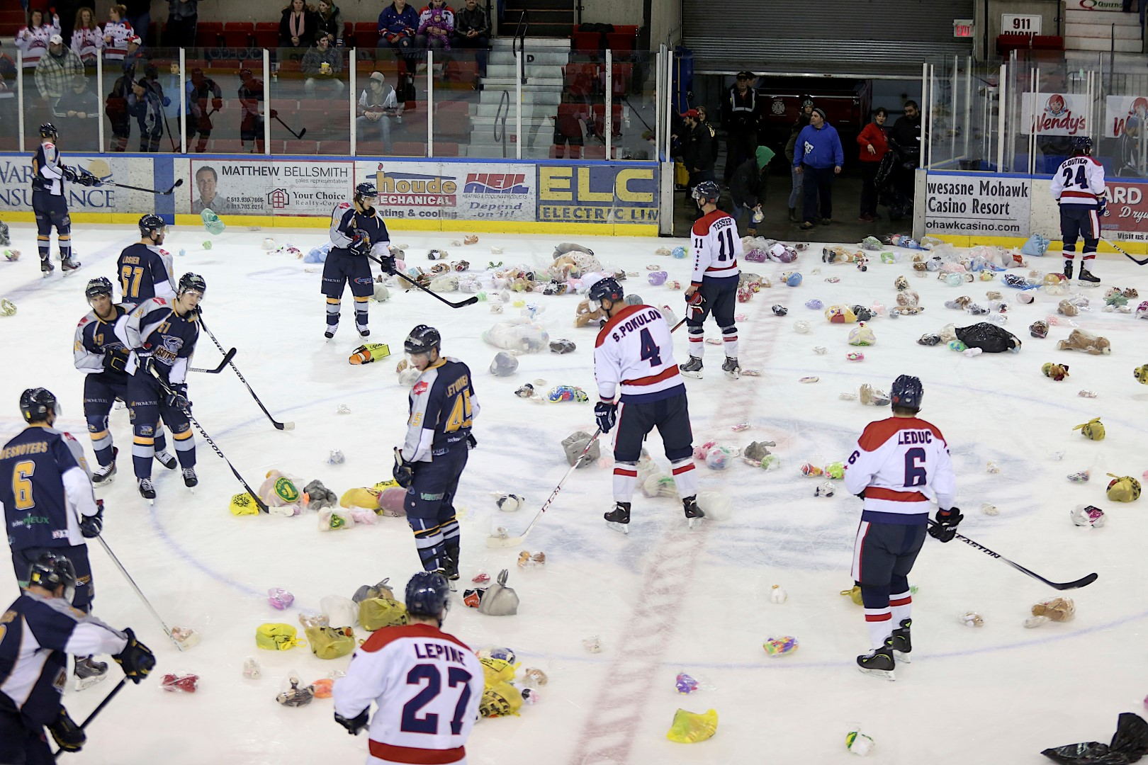 Players with the Thetford-Mines Isothermic and the Cornwall River Kings help pick up 750 teddy bears off the ice after their game Dec. 20, 2014. The toys were given to Sparky's Toy Drive. (Photo/Allison Papineau)