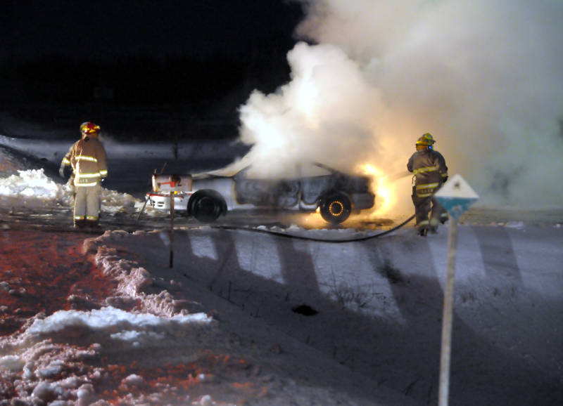 Firefighters battle a car fire on Jan. 5, 2015, about three kilometers north of St. Andrews West on Highway 138. The owner had been having car trouble prior to the fire, according to the assistant deputy fire chief. (Cornwall Newswatch/Bill Kingston)