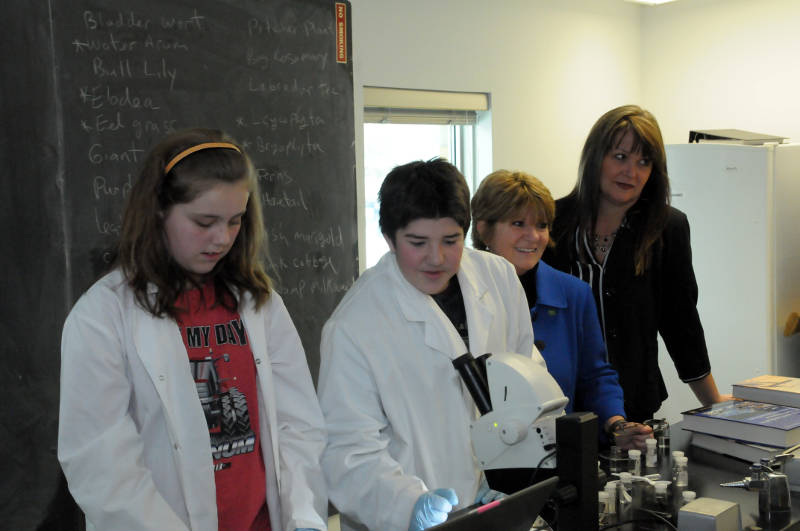 Students Carly Walker and James Lauzon check on a specimen in the microscope while TD Canada Trust Branch Managers observe the class. The bank has given $30,000 for education programs at the River Institute this year. (Cornwall Newswatch/Bill Kingston)