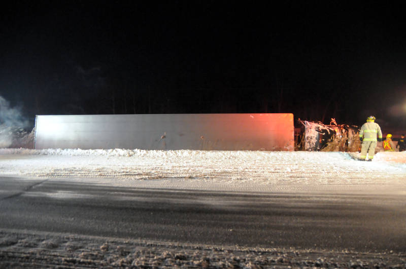 Firefighters and an O.P.P. officer survey the damage after freeing the driver of this big rig following a single-vehicle crash on Highway 401 Feb. 2, 2015 just west of Boundary Road. (Cornwall Newswatch/Bill Kingston)