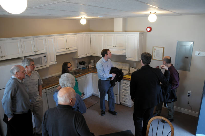 Members of the Cornwall Wesleyan Church show off their new disaster relief center on Feb. 28, 2015, which will house a family of four for up to a month. Rev. Larry Blaikie (black suit) shows of the kitchen to MP Executive Assistant Eric Duncan, center, while Acting Cornwall Mayor Carilyne Hebert (green jacket) listens. (Cornwall Newswatch/Bill Kingston)