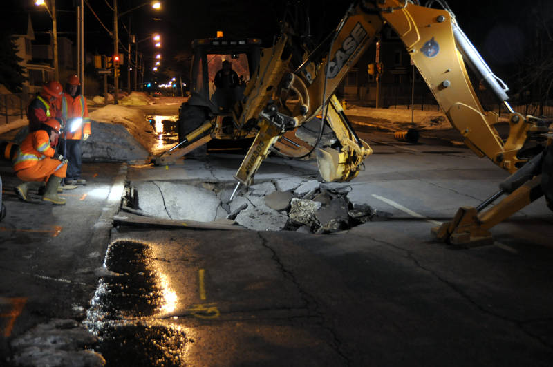 Three public works employees check where a backhoe with a jack hammer is excavating the site of a sinkhole on Fifth Street East in the early morning hours of March 12, 2015. A water main break caused part of the street to collapse. (Cornwall Newswatch/Bill Kingston)