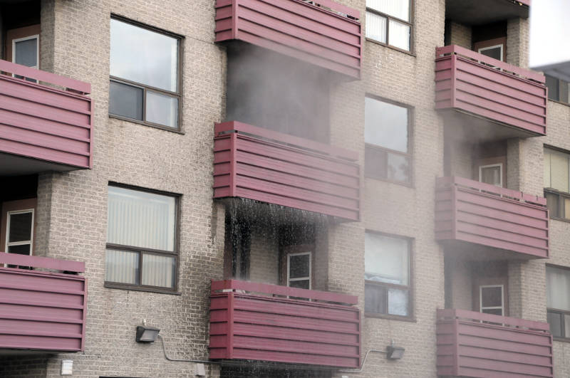 Water pours off a third floor balcony at Residence Edward after a fire in an apartment at the social housing complex on April 5, 2015. (Cornwall Newswatch/Bill Kingston)