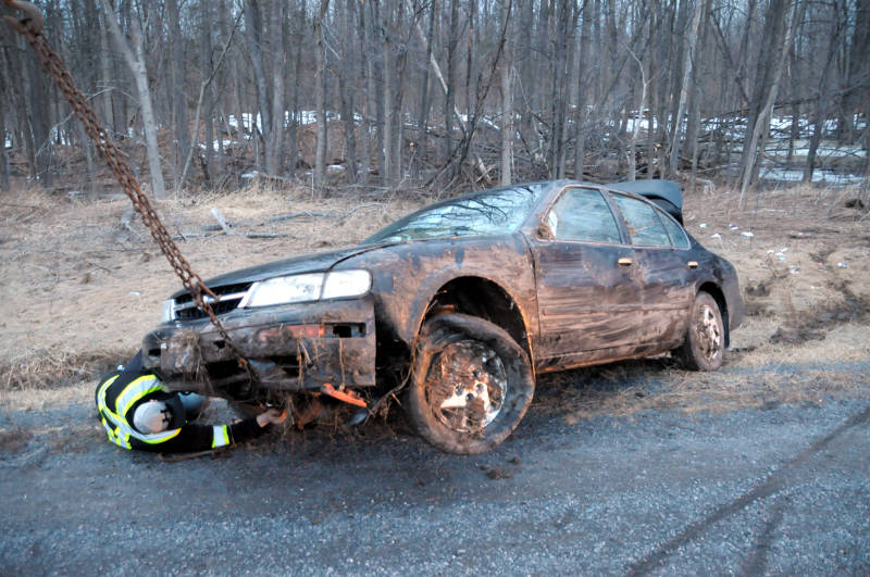Tow truck driver Phillipe Boyer hooks the chains on this Nissan Maxima after a rollover on Highway 401 in the westbound lanes on April 3, 2015. A family of four were lucky to walk away without any injuries. (Cornwall Newswatch/Bill Kingston)