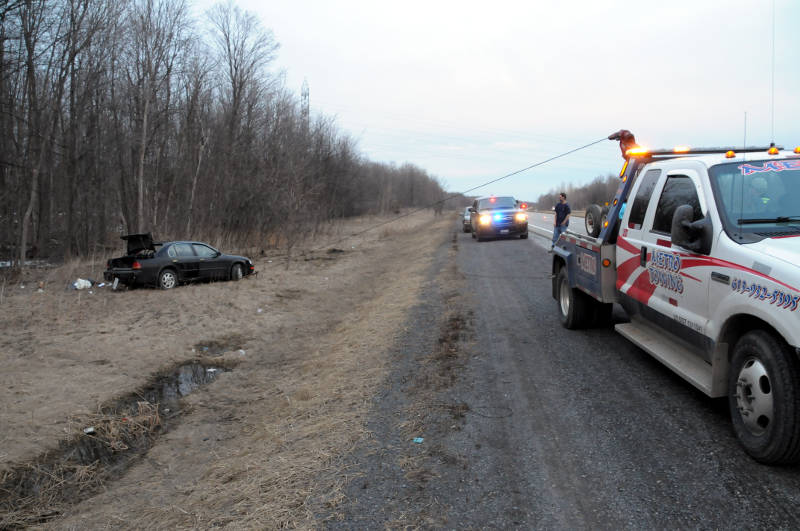 A tow truck starts pulling this car out of the ditch on the westbound Highway 401 in South Stormont after a single vehicle crash on April 3, 2015. (Cornwall Newswatch/Bill Kingston)