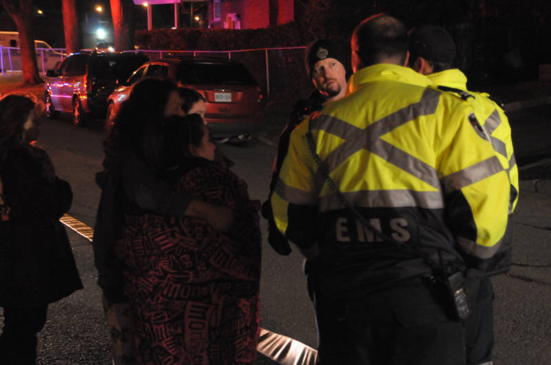A woman, who identified herself as one of the occupants, clutches two children while speaking with police and paramedics. No one was injured in the fire April 23, 2015. (Cornwall Newswatch/Bill Kingston)