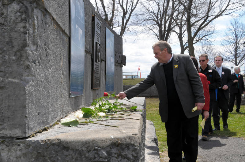 Cornwall, Ont. mayor Leslie O'Shaughnessy places a red rose on the Workers' Memorial in Lamoureux Park as part of the National Day of Mourning for killed and injured workers. (Cornwall Newswatch/Bill Kingston)