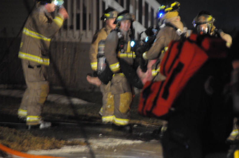 Firefighters carry a badly-burned man from the back of the multi-unit apartment building on Sixth Street West on April 3, 2015. (Cornwall Newswatch/Bill Kingston)
