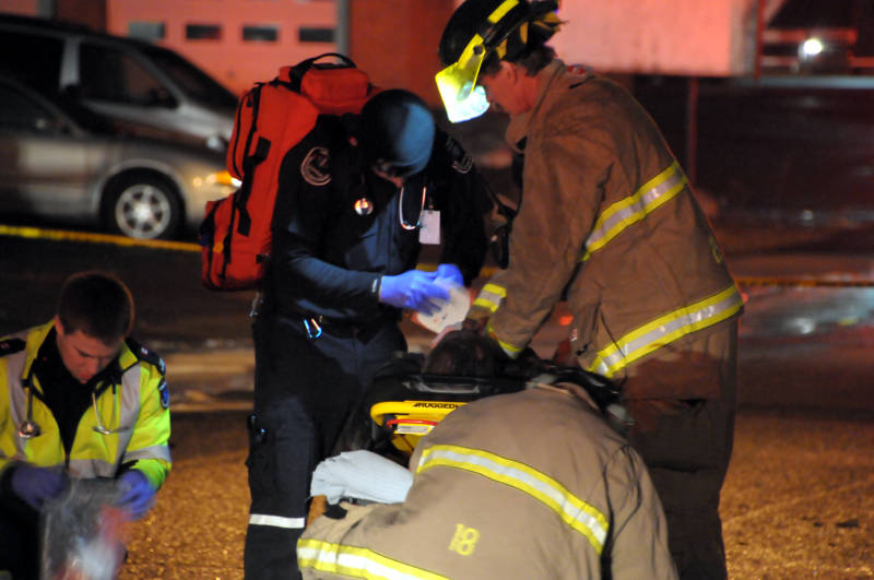 A Cornwall firefighter performs chest compressions on a fire victim while a paramedic performs his duties while waiting for an ambulance to get into position to load the patient after a multiplex fire on Sixth Street West on April 3,2015. (Cornwall Newswatch/Bill Kingston)