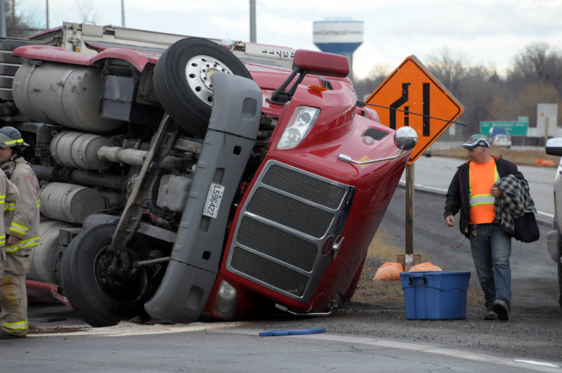 This unidentified truck driver looks at what's left of his rig after the truck tipped over on the Highway 401 westbound on-ramp at Brookdale Ave. on April 20, 2015. The trucker was not injured. (Cornwall Newswatch/Bill Kingston)