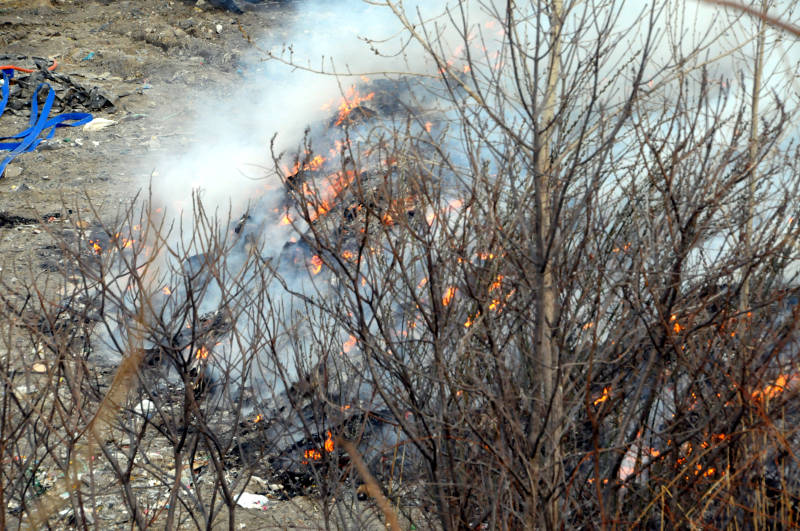 Flames dart between piles of garbage in the Cornwall landfill April 18, 2015. It's not known what started the fire which kept firefighters on scene for several hours and taxed their resources. (Cornwall Newswatch/Bill Kingston)