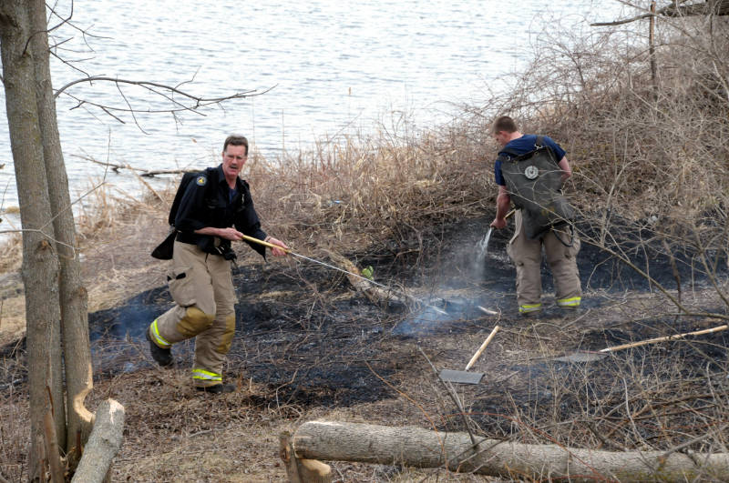 Firefighters use water packs to put out this grass fire along the waterfront trail near the Rotary Eco-Garden. It was one of three grass fires within 24 hours in the city. (Cornwall Newswatch/Bill Kingston)