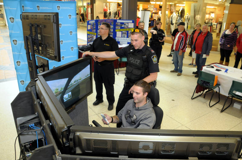 Leo Paul Marion of Ingleside attempts to send a text while operating the distracted driving simulator at Cornwall Square May 11, 2015. Const. Matt Dupuis watches his progress. The simulator is part of a number events for Police Week. (Cornwall Newswatch/Bill Kingston)