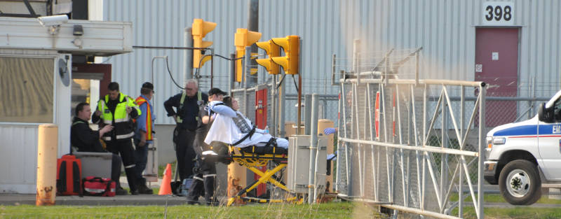 A woman is taken away by paramedics on a stretcher while another man, seated, is checked over by paramedics. Emergency crews were called May 1, 2015 after an explosion and fire involving a tanker truck on the property. (Cornwall Newswatch/Bill Kingston)