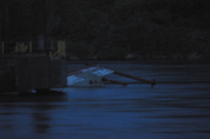 A portion of a tug boat (white) sticks out of the St. Lawrence River next to a barge after capsizing around 9 p.m. June 22, 2015. This was the second tug to go under trying to position the barge for work on the north channel bridge. Transport Canada is leading a plan for righting the vessels, according to the Ontario Ministry of Environment. (Cornwall Newswatch/Bill Kingston)