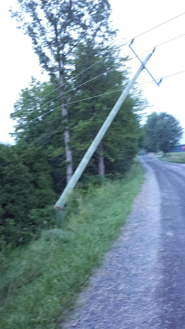 A hydro pole on Heron Road, west of Williamstown, Ont., is snapped off at the base, a likely cause of a massive outage in South Glengarry July 14, 2015. Hydro One doesn't expect to have the power back on until 2 a.m. July 15, 2015. (Photo/Bryan Ward)