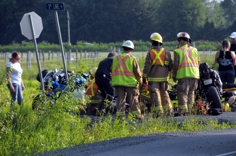 South Glengarry firefighters and SD&G paramedics aid a rider on the ground on July 5, 2015 after a single vehicle crash. The sportbike landed in a deep ditch after failing to negotiate a tight curve in South Service Road. (Cornwall Newswatch/Bill Kingston)