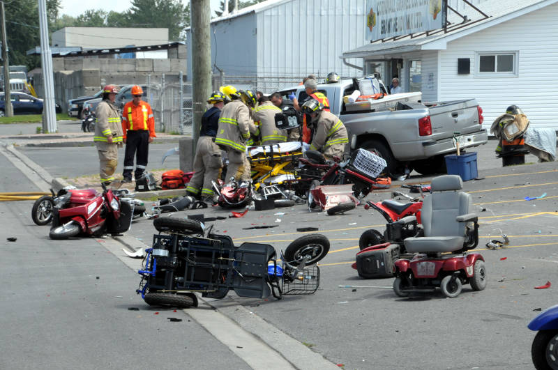 Cornwall paramedics and firefighters work to free the driver of this pickup truck after a crash on Eleventh Street West on July 30, 2015. Witnesses said they heard the truck accelerate hard several hundred feet down the street before it plowed into a stand of e-bikes and struck a hydro pole. (Cornwall Newswatch/Bill Kingston)
