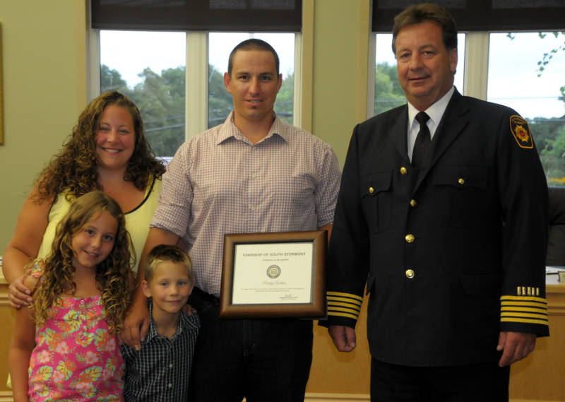 Rodney Wilson of Long Sault receives a certificate of recognition from South Stormont Fire Chief Gilles Crepeau for his heroic efforts in saving a couple on Hoople Bay last month. Joining Rodney in receiving the certificate Aug. 12, 2015 are his wife, Adele, and children Isabella, 9, and Zachary, 6. (Newswatch Group/Bill Kingston)