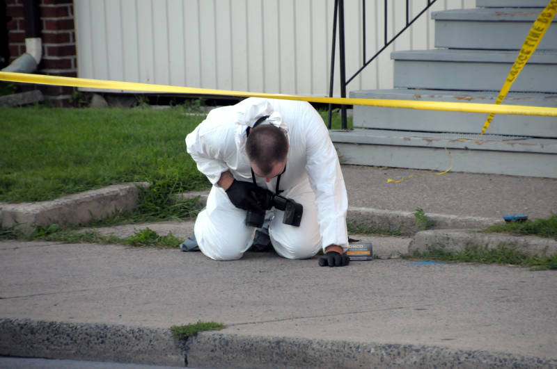 A Cornwall police forensics investigator gets down on his knees to inspect some possible evidence on the sidewalk after the death of a man at this Marlborough Street apartment complex Aug. 3, 2015. (Cornwall Newswatch/Bill Kingston)