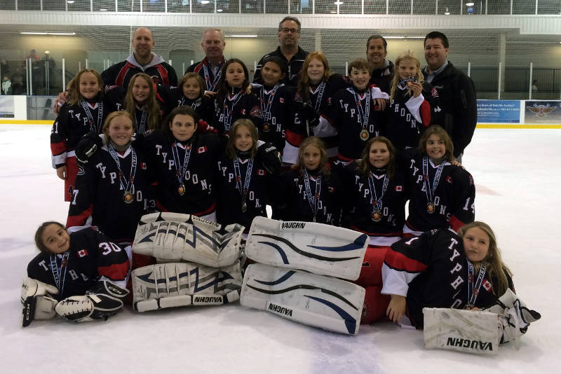 The Cornwall Atom Typhoons celebrate with their silver medal. Pictured are: Front Row: Amelie Brunet and Emily McLaughlin; Second Row: Ella Dickson, Olivia Laplante, Peyton Cicchini, Emily Bethune, Julia Murphy and Elizabeth Arbic; Third Row: Julia Cameron, Kristen Zeran, Ryese Brownell, Olivia Carter, Paisley Cook, Isabella Vincent, Ava Bellefeuille and Maude Millet; Back Row: Keith Dickson (Assistant Coach), Earl McBean (Assistant Coach), Ian Laplante (Head Coach), Christine Cicchini (Trainer) and Alain Bellefeuille (Manager). (Photo/Supplied)