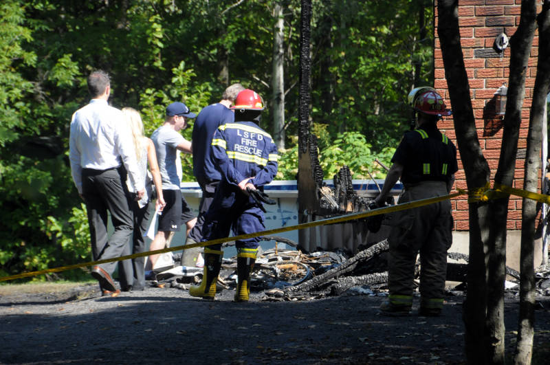 A young man, who identified himself as 'Tyler', is led into the scene by O.P.P. investigators and the Ontario Fire Marshal investigator to survey the damage. The man told investigators he grew up in the home. (Newswatch Group/Bill Kingston)