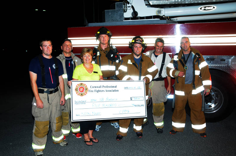 Members of Cornwall Fire Department present Canadian Cancer Society of SDG & Prescott-Russell Manager Carolyn Bourassa with a cheque for $500 during the Neon Night walk for childhood cancer Sept. 25, 2015. (Newswatch Group/Bill Kingston)