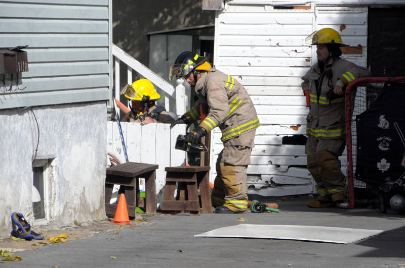 Firefighters use a heat-sensing device to check for any hot spots under the back porch of an Ontario Street home on Oct. 2, 2015 after a smoking-related fire. (Newswatch Group/Bill Kingston)