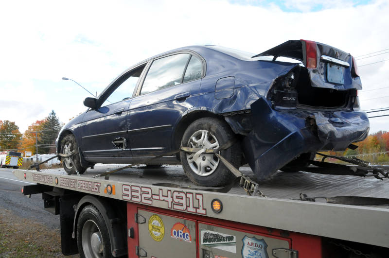 A Honda Civic with extensive rear-end damage is loaded on a tow truck after a two vehicle crash on Vincent Massey Drive in Cornwall, Ont. on Oct. 18, 2015. (Newswatch Group/Bill Kingston)