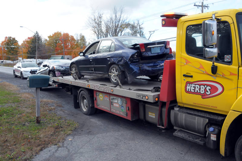 A tow truck driver (not shown) makes some final adjustments before hauling away two vehicles involved in a crash on Vincent Massey Drive on Oct. 18, 2015. One person was hospitalized as a precaution. (Newswatch Group/Bill Kingston)