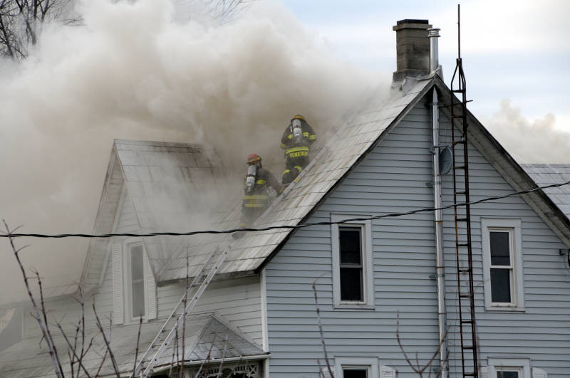 Two firefighters, nearly 30 feet off the ground, get ready to cut a hole in the roof of this farm house Dec. 13, 2015. The fire on County Road 18, east of Gallingertown, causing extensive damage. (Newswatch Group/Bill Kingston)