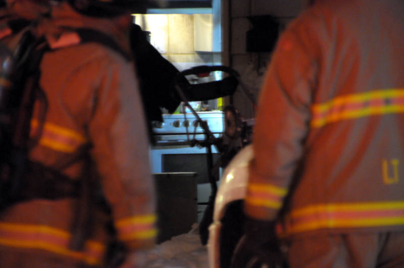 Firefighters search with flashlights through the rear unit of a triplex at 34 Lauber Avenue in Cornwall, Ont. on Dec 30, 2015. The fire has been turned over to police for an investigation. (Newswatch Group/Bill Kingston)