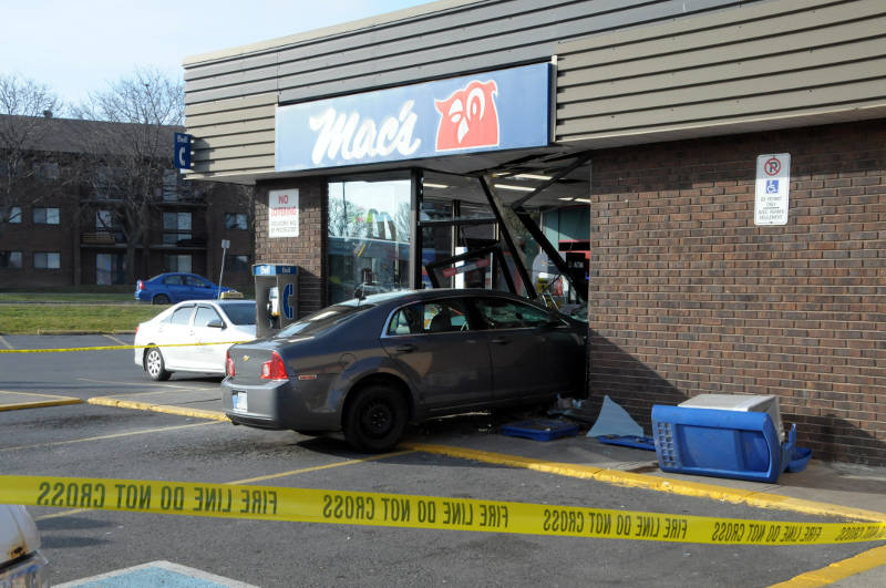 A sedan plows through the front of a Mac's convenience store in Cornwall, Ont. on Dec. 6, 2015. Two people in the vehicle were checked over by paramedics as a precaution. Police say nobody inside the store was hurt, (Newswatch Group/Bill Kingston)