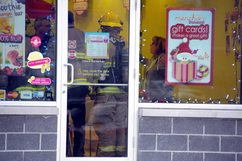 Menchie's Cornwall owner Jennifer Jurchuk speaks with police and firefighters Dec. 10, 2015 after discovering something suspicious in a delivery to the store. (Newswatch Group/Bill Kingston)