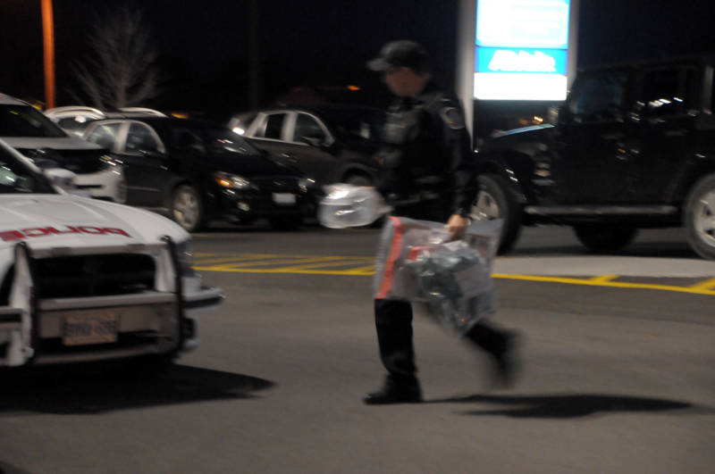 Cornwall police Const. Justin Wheeler carries evidence bags to his cruiser Dec. 10, 2015 from Menchie's on Ninth Street East in Cornwall, Ont. Police and firefighters were called to a report of a suspicious package, which has been seized for further testing. (Newswatch Group/Bill Kingston)