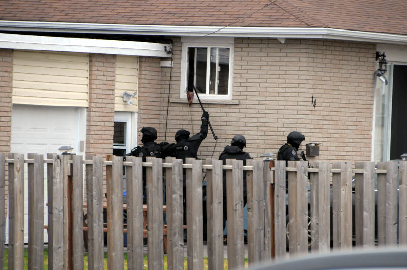 A police officer uses a special camera on a pole to look inside a house on Cariere Avenue Dec. 18, 2015 during an all-day standoff. Officers later entered the building and found it empty. (Newswatch Group/Bill Kingston)