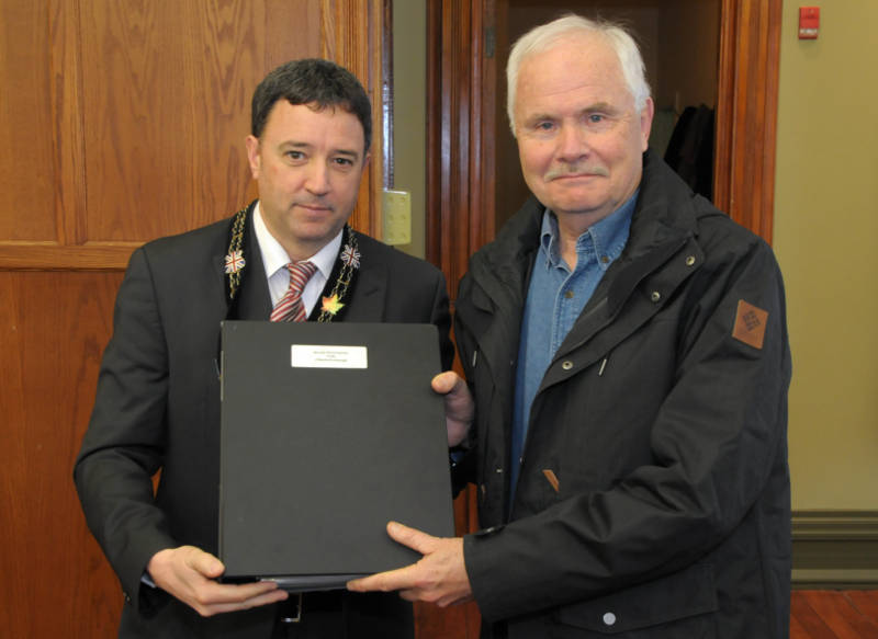 SD&G Warden Jamie MacDonald presents a volume of historical documents to Glengarry County Archivist Allan MacDonald during a presentation Feb. 16, 2016 at the United Counties building in Cornwall, Ont. The donation will be preserved at the archive building in Alexandria. (Newswatch Group/Bill Kingston)