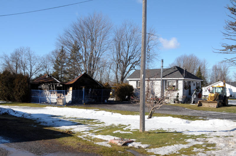 A garage fire at this Osnabruck Center, Ont. home on Jan. 28, 2016 gutted the building and melted the siding on the nearby house. A man was treated for burns to his face and arms after the flash fire. (Newswatch Group/Bill Kingston)