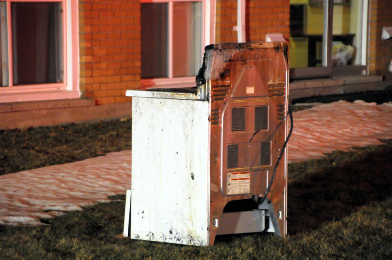 A charred stove sits on the front lawn of a row house complex on St. Michel Avenue in Cornwall, Ont. after a fire Feb. 4, 2016. A fire investigator says the unit the stove was in has extensive smoke damage. (Newswatch Group/Bill Kingston)
