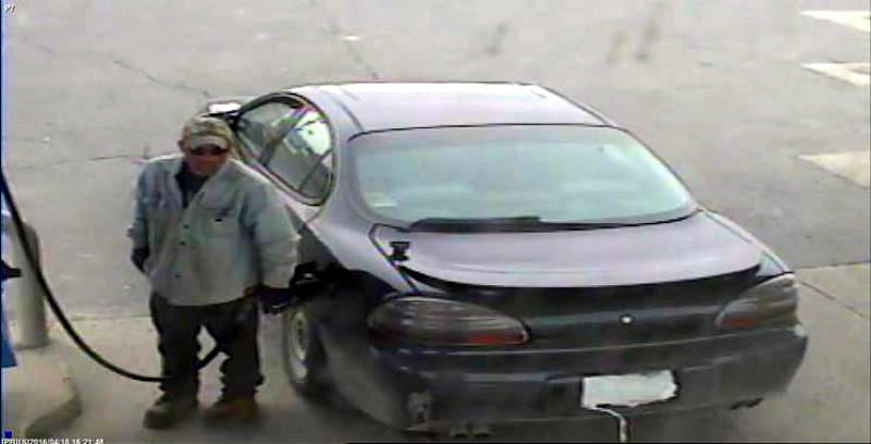 In this Monday, April 18, 2016 photo provided by SD&G O.P.P., plastic bags cover the licence plate of a car as a man fuels up at the Monkland Esso. The suspect is wanted for stealing fuel from the gas station on Highway 138. (SD&G O.P.P. via Newswatch Group)